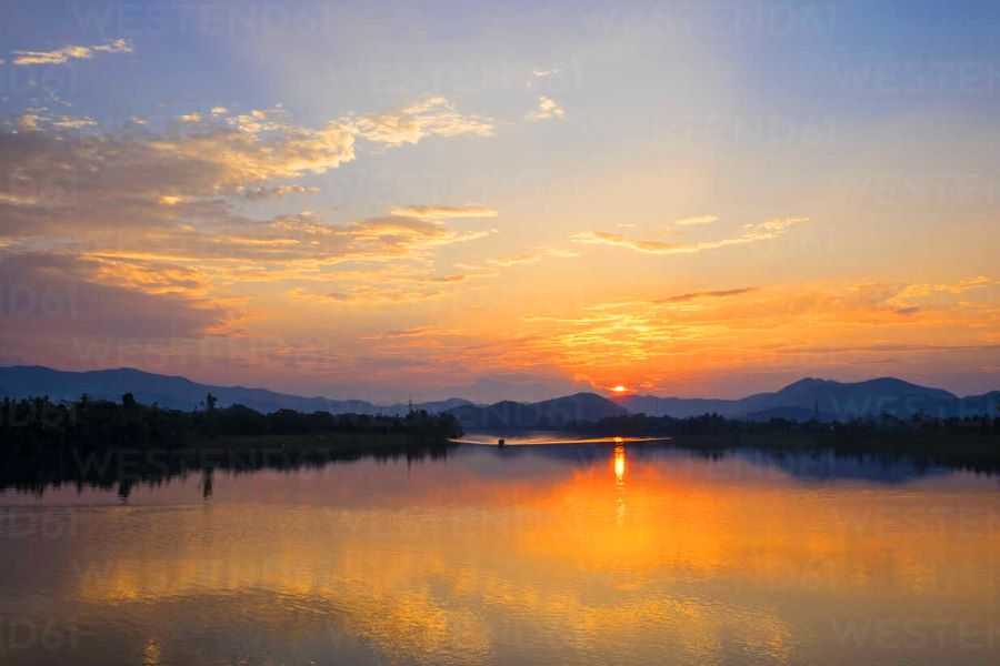 sunset over perfume river in hue